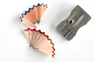 Small metal sharpener with pencil shavings on white